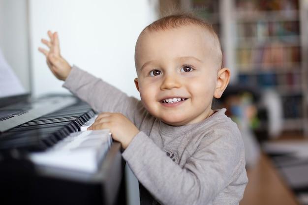 Ein kleinkind steht am klavier und lächelt.