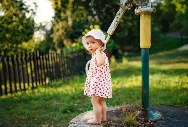 Ein kleinkindmädchen, das im sommer draußen im garten steht. platz kopieren.