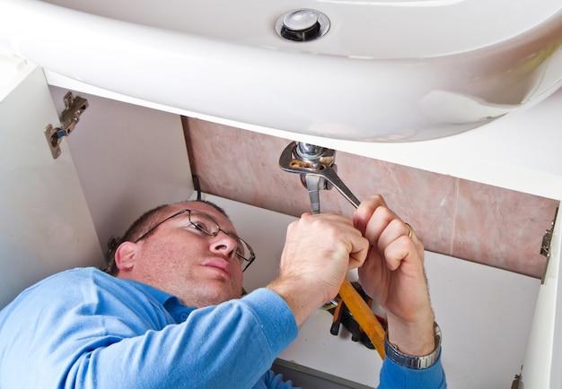 Ein klempner, der eine defekte wanne im badezimmer repariert