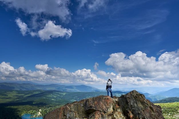Ein kletterer steht am rand einer klippe und schaut in die ferne auf den see und die berge. altai russland