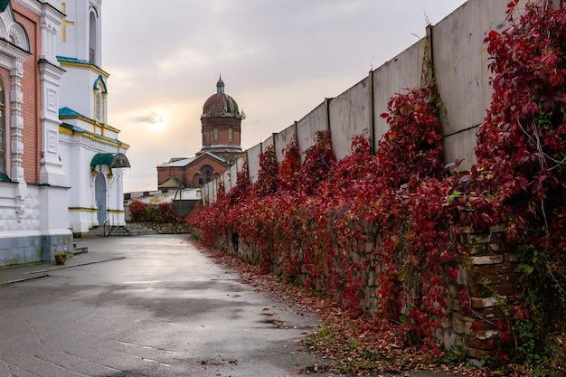 Ein klosterhof mit einem hohen zaun, der ihn von einer verlassenen, nicht wieder aufgebauten kirche trennt
