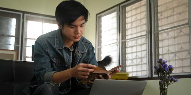Ein kluger mann liest ein buch, während er arbeitet und vor einem computer-laptop sitzt