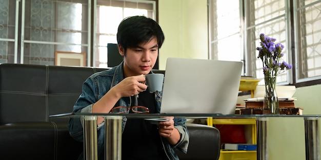 Ein kluger mann trinkt einen kaffee, während er arbeitet und vor einem computer-laptop sitzt