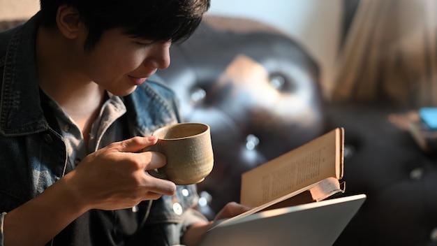 Ein kluger mann trinkt einen kaffee, während er ein buch liest und am schwarzen ledersofa sitzt