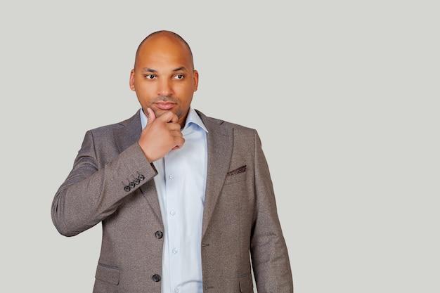 Ein kluger, selbstbewusster junger afroamerikaner in einem anzug hält sein kinn und schaut nachdenklich zur seite
