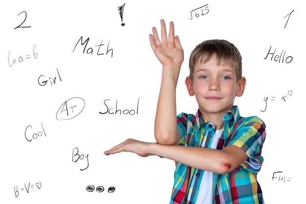 Ein kluger, süßer junge hebt seine hand, um im unterricht zu antworten. glückliches kind gegen ein weißes brett mit aufschriften. bildungskonzept, konzept zurück zur schule