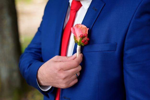 Ein knopfloch hält dem verlobten eine hand