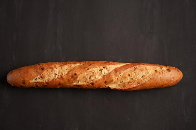 Ein knuspriges französisches baguette liegt aus dunkelschwarzen sesamkörnern mit tischhintergrund