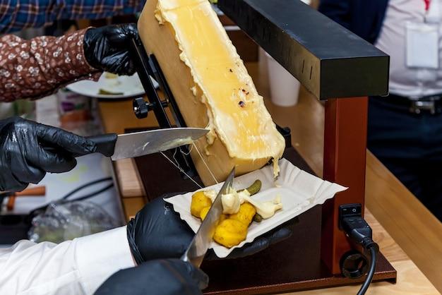 Ein koch bereitet mit einem speziellen instrument zum schmelzen von käse ein gericht mit raclette zu.