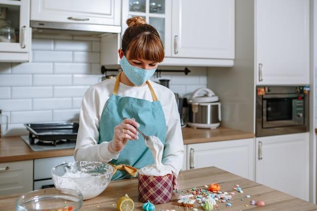 Ein koch in einer medizinischen maske und handschuhe in einer wohnküche setzen süße figuren auf das sahnehäubchen eines osterkuchens