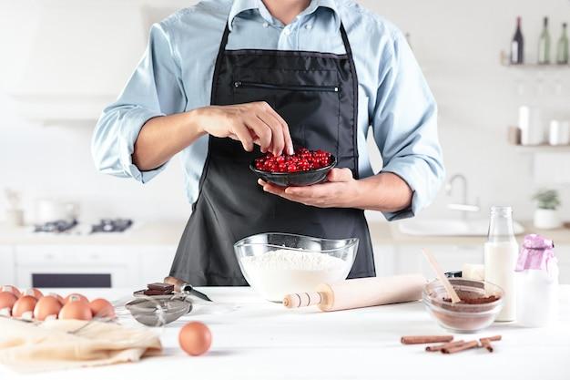 Ein koch in einer rustikalen küche. die männlichen hände mit zutaten zum kochen von mehlprodukten oder teig, brot, muffins, kuchen, torte, pizza