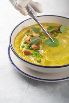 Ein koch in handschuhen dekoriert eine suppe aus püriertem bio-gemüse mit crackern, grünen erbsen und kräutern mit basilikumblättern