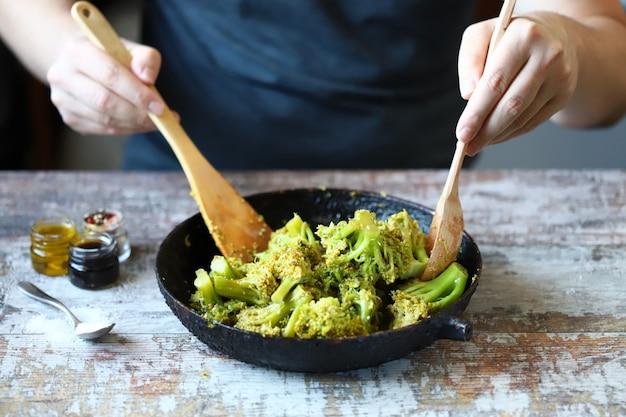 Ein koch mit einem holzspatel und einem löffel mischt brokkoli in einer pfanne.