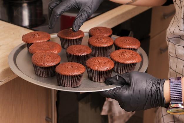Ein koch mit handschuhen hält ein tablett mit schokoladenmuffins in der hand