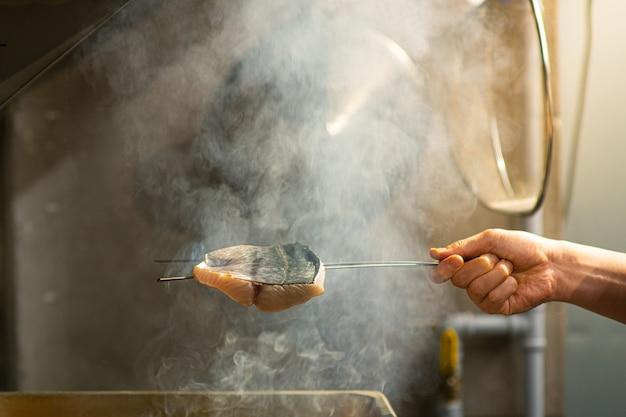 Ein koch räuchert einen fisch