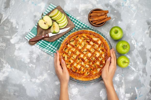 Ein köstlicher apfelkuchen der draufsicht, der durch frau mit frischen grünen apfelkuchen-kekszuckerfrüchten hält