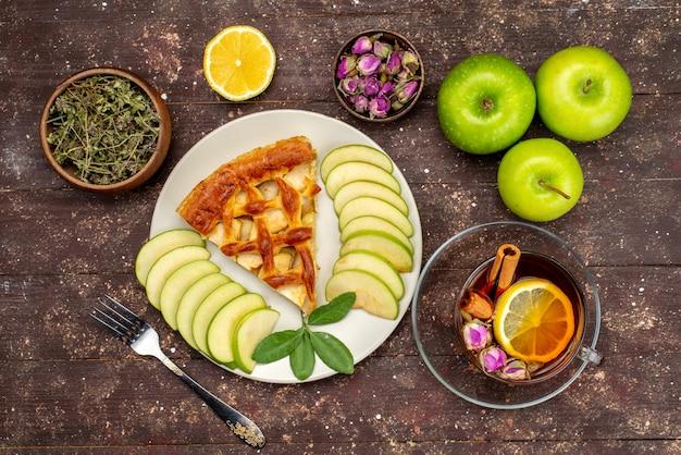 Ein köstlicher apfelkuchen der draufsicht mit frischen grünen äpfeln des tees auf dem hölzernen schreibtischkuchenplätzchenzuckerdesserttee