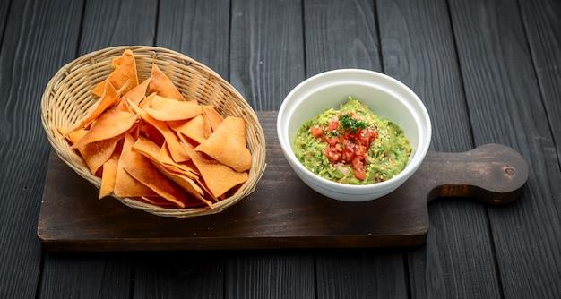 Ein köstlicher authentischer mexikanischer guacamole-dip mit avocado, limette und tomate.