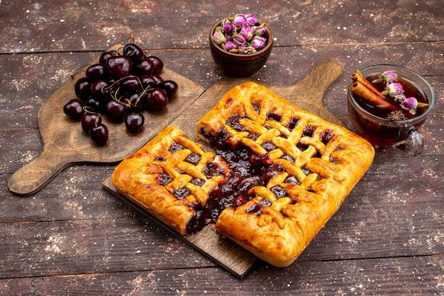 Ein köstlicher erdbeerkuchen der draufsicht mit erdbeergelee-kirschen und tee auf dem hölzernen hintergrundkuchen-kekszucker