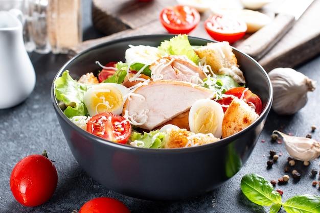 Ein köstlicher hähnchen-caesar-salat mit parmesan, dressing und croutons auf dunklem hintergrund