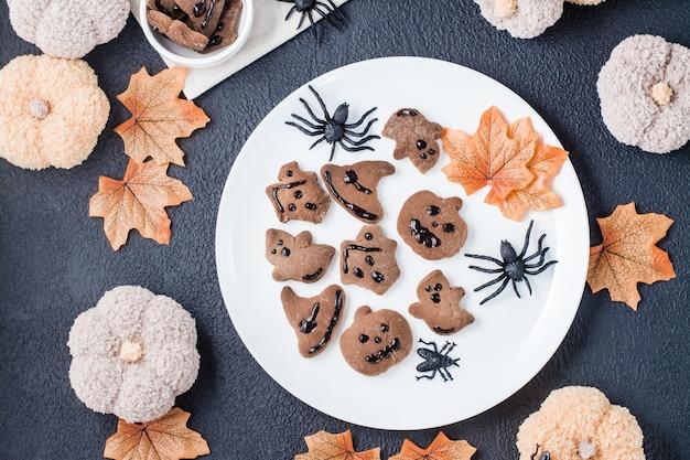 Ein köstlicher halloween-genuss - lebkuchen mit schokoladenglasur in schalen auf einem tisch mit kürbissen, blättern und spinnen. traditionelle feier. ansicht von oben