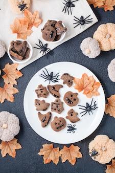 Ein köstlicher halloween-genuss - lebkuchen mit schokoladenglasur in schalen auf einem tisch mit kürbissen, blättern und spinnen. traditionelle feier, süßes essen. ansicht von oben und vertikal
