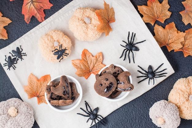 Ein köstlicher halloween-genuss - lebkuchen mit schokoladenglasur in schalen auf einem tisch mit kürbissen, blättern und spinnen. traditionelle feiern. ansicht von oben
