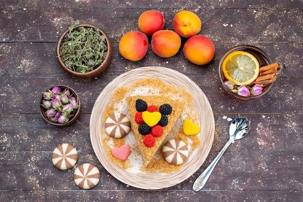 Ein köstlicher honigkuchen der draufsicht mit bonbonhonig und pfirsichen auf dem dunklen hintergrundkuchen-tee-bonbonhonig