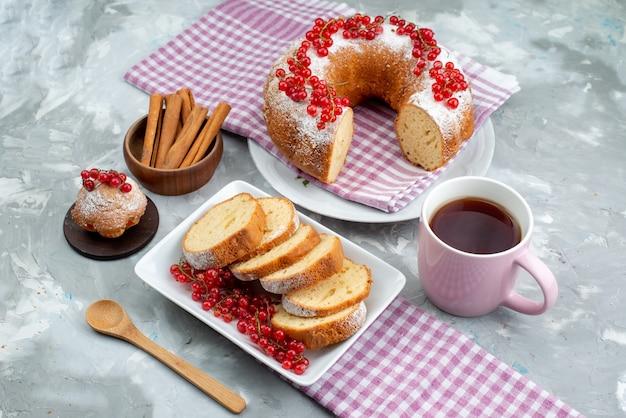 Ein köstlicher kuchen der draufsicht mit frischem zimt der roten preiselbeeren und tee auf der weißen schreibtischkuchen-keks-tee-beere