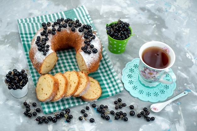 Ein köstlicher kuchen der draufsicht mit frischen blaubeeren und tee auf dem weißen schreibtischkuchen-keks-tee-beerenzucker