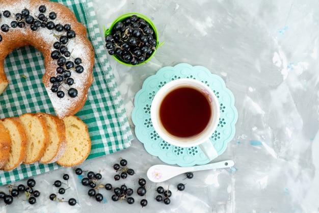 Ein köstlicher kuchen der draufsicht mit frischen blaubeeren und tee auf der weißen schreibtischkuchen-keks-tee-beere