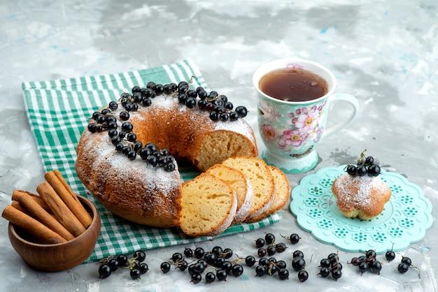 Ein köstlicher kuchen der vorderansicht mit frischen blaubeeren und tee auf dem weißen schreibtischkuchen-keks-tee-beeren-zuckerdessert