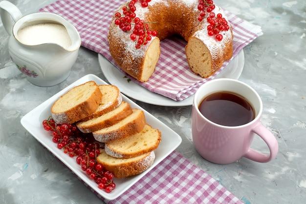 Ein köstlicher kuchen der vorderansicht mit frischen roten preiselbeeren und tee auf der weißen schreibtischkuchen-keks-tee-beere