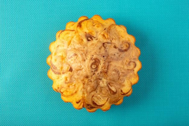 Ein köstlicher leckerer schokokuchen des runden süßen kuchens der draufsicht auf dem karierten blauen hintergrundzucker-tee-keksauflauf