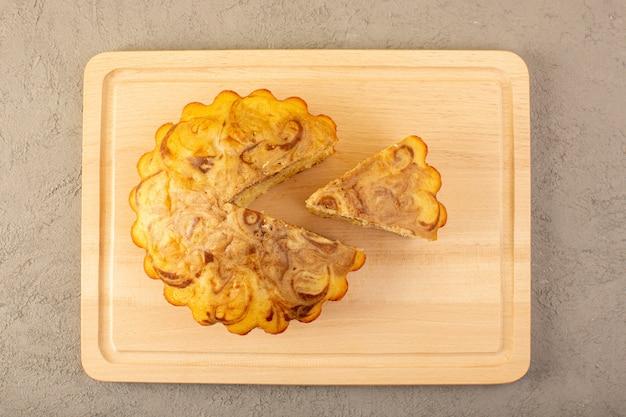 Ein köstlicher leckerer schokoladenkuchen der süßen ansicht der draufsicht, der auf dem cremefarbenen quadratischen schreibtisch auf dem grauen hintergrundzucker-tee-keksauflauf geschnitten wird