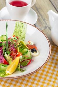 Ein köstlicher räucherlachs-gartensalat mit räucherlachs, gemischtem babygrün