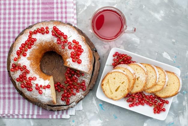 Ein köstlicher runder kuchen der draufsicht mit frischen roten preiselbeeren und preiselbeersaft auf dem weißen schreibtischkuchen-kekstee-beerenzucker