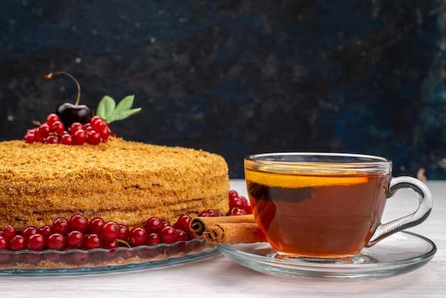 Ein köstlicher und mit roten preiselbeeren und tee auf dem grauen schreibtischkuchen-kekszuckerfoto gebackener runder honigkuchen der vorderansicht