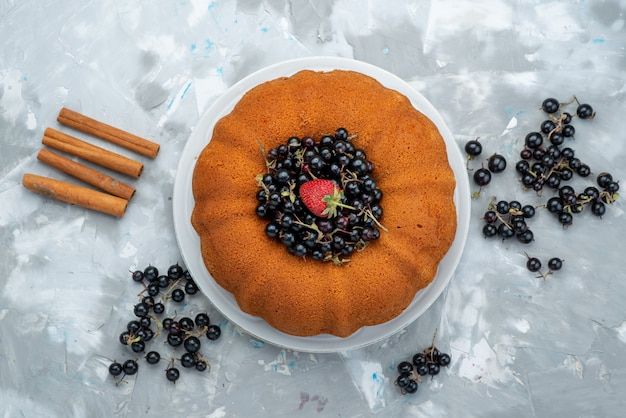 Ein köstlicher und runder obstkuchen von oben mit frischem blau, beeren auf hellem kuchenkeks und süßem zucker