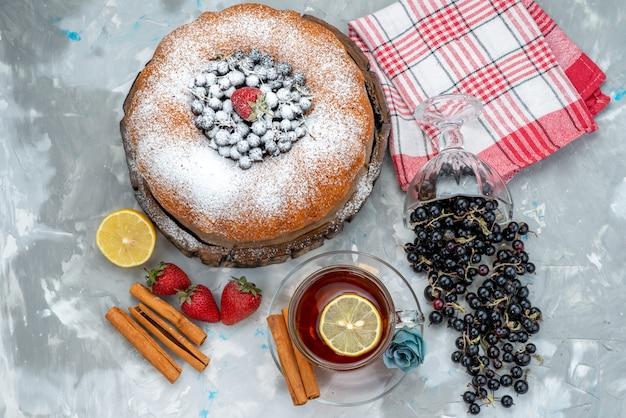 Ein köstlicher und runder obstkuchen von oben mit frischem blau, beeren und tee auf hellem kuchenkeks süßem zucker