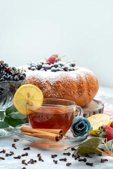 Ein köstlicher und runder obstkuchen von vorne mit frischem blau, beeren und einer tasse tee auf hellem, süßem zucker aus kuchen