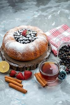 Ein köstlicher und runder obstkuchen von vorne mit frischem blau, beeren und tee auf hellem, süßem zucker aus kuchenkeksen