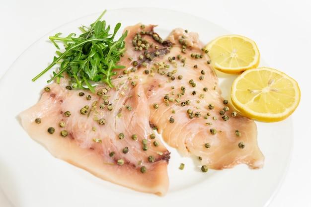 Ein köstliches carpaccio aus frischem schwertfisch, gewürzt mit olivenöl extra vergine, schnittlauch und ein paar tropfen zitronensaft