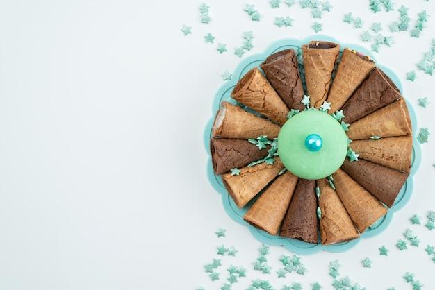 Ein köstliches eis der draufsicht mit hörnern und grünem französischem macaron auf weißer keksfarbe des dessertkuchens