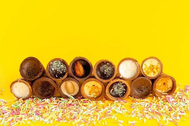 Ein köstliches eis der vorderansicht mit bunten bonbons auf gelber, süßer zuckerfarbe