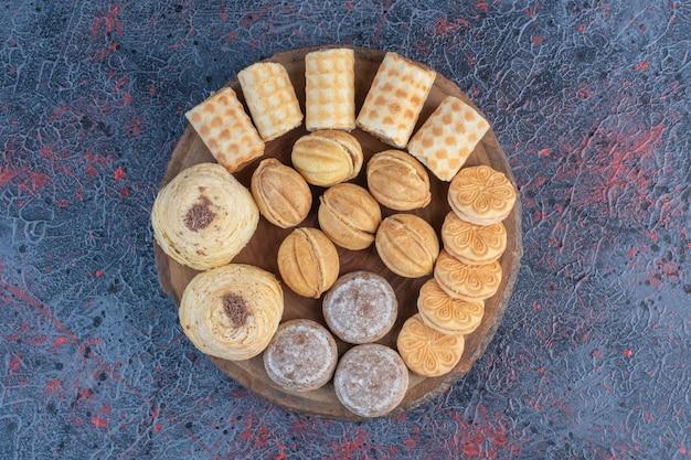 Ein köstliches gebäcksortiment auf einem holzbrett auf abstraktem tisch. Kostenlose Fotos
