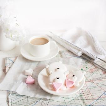 Ein köstliches marshmallow-dessert in form von bären und eine tasse mit einem getränk auf dem schreibtisch