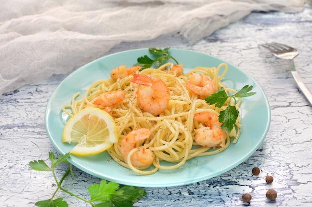 Ein köstliches spaghetti-rezept mit garnelen und pfeffer, dekoriert mit zitrone und pfeffer.