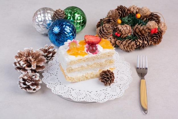 Ein köstliches stück kuchen mit tannenzapfen auf weißem hintergrund. hochwertiges foto