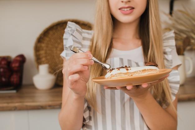 Ein konditor oder eine hausfrau in einer gestreiften schürze schmückt eine eclair closeup süßwaren